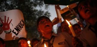Mujeres sostienen velas y carteles mientras gritan (© AP Images)