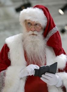 Santa holding mobile phone (© AP Images)