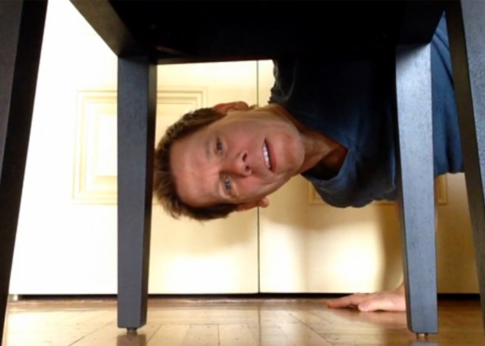 Kevin Bacon crouching under table (YouTube)
