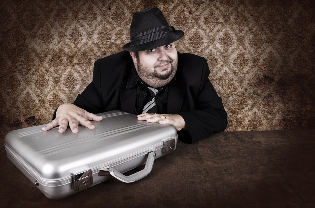 Man in black hat furtively touching silver metal briefcase (Shutterstock)