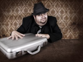یک مرد با یک کلاه سیاه پنهانی به یک کیف نقره ای دست می زند (Shutterstock)