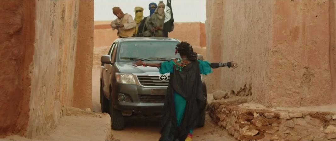 امرأة تعترض طريق سيارة في حين يشير ركابها البنادق في وجهها (Cohen Media Group)