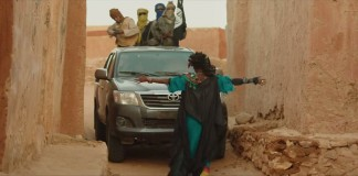 Woman blocking sport utility vehicle while its passengers point guns at her (Cohen Media Group)
