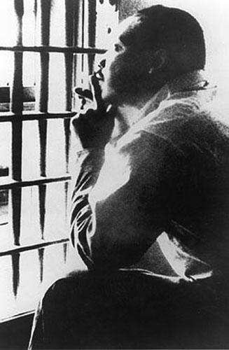 Martin Luther King seated, looking upward through jail cell bars (National Archives)