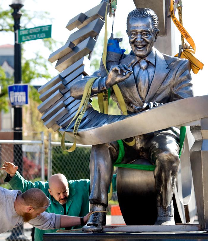 رجال يُركّبون تمثال ديوك إلينغتون وهو يعزف على البيانو (© Tim Cooper)