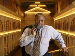 Lonnie Bunch standing with his suit jacket slung over his shoulder (© AP Images)