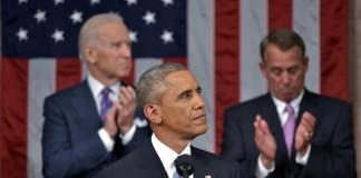 الرئيس أوباما وراء الميكروفون، ويظهر وراءه نائب الرئيس بايدن وجون بينر (© AP Images)