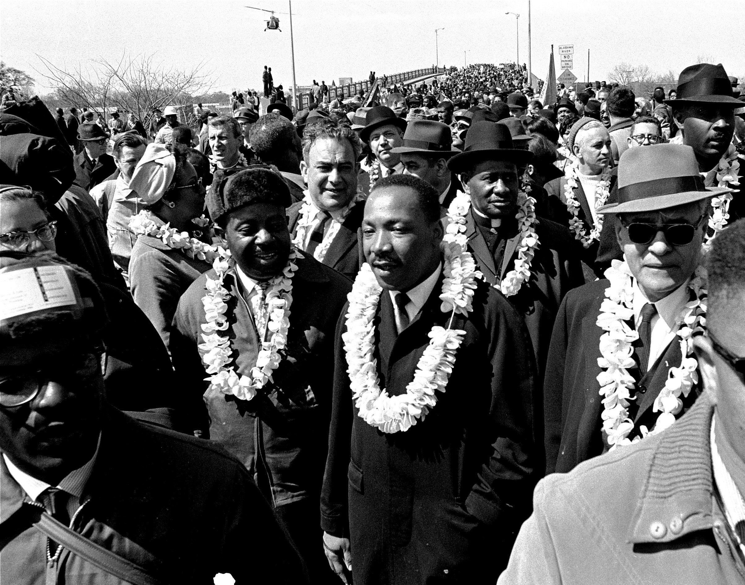 Martin Luther King leading throng of marchers across bridge (© AP Images)