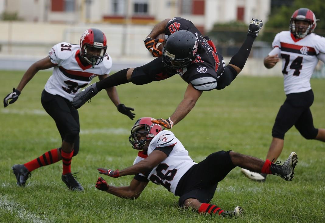 Un jugador de fútbol americano vuela en el aire en medio de otros jugadores (© AP Images)