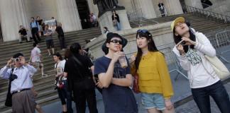 参观纽约证券交易所的中国游客(© AP Images)