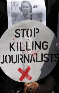 يد تحمل لافتة احتجاجا على قتل الصحفيين (AP Images)