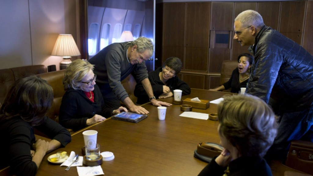 George W. Bush showing photos to Michelle Obama, Hillary Clinton, Obama staff and Cabinet members, and Laura Bush, gathered around table (White House)