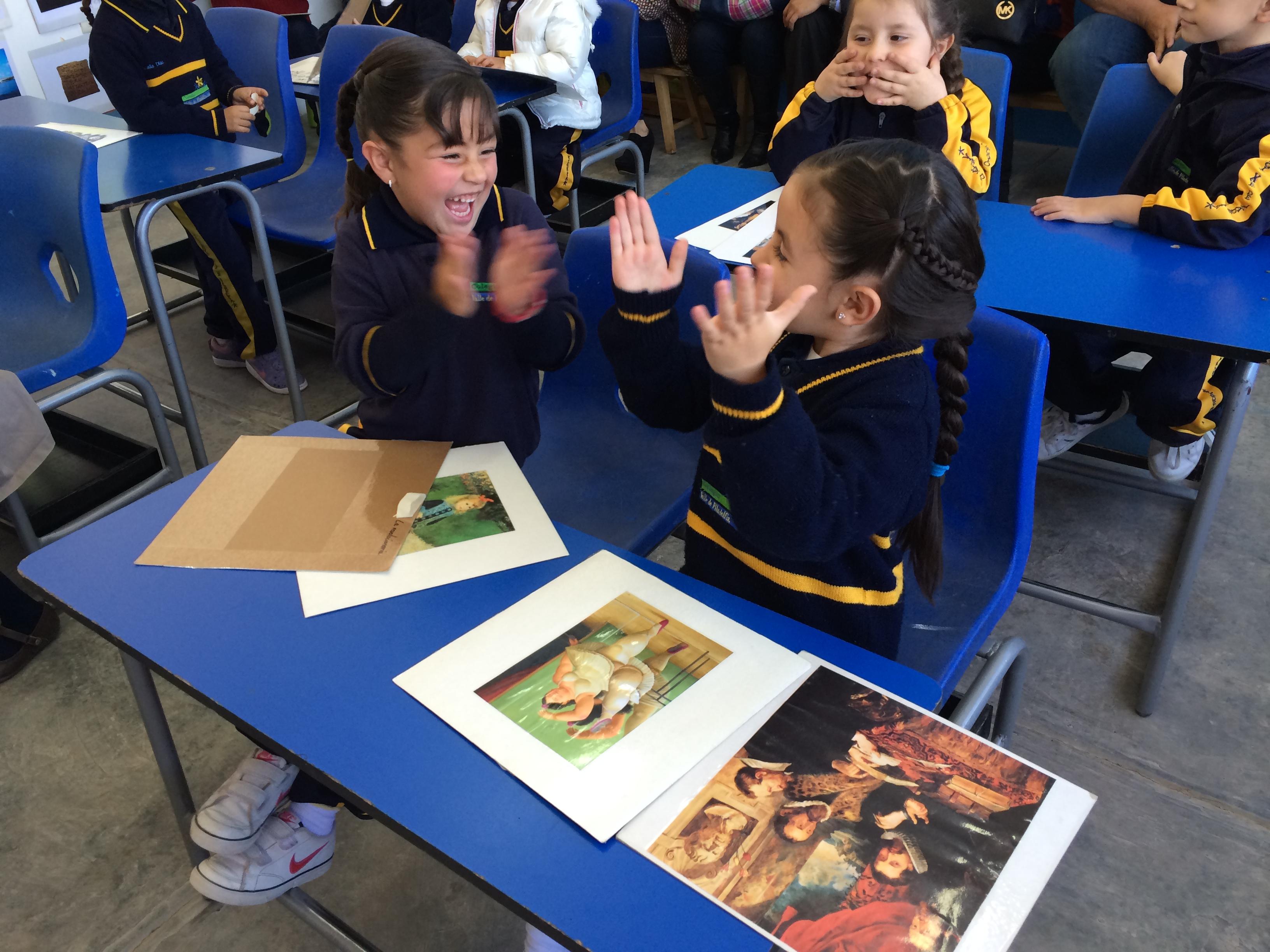 طفلتان جالستان على مقاعد دراسية تضحكان (Courtesy of Colegio Valle de Filadelfia)