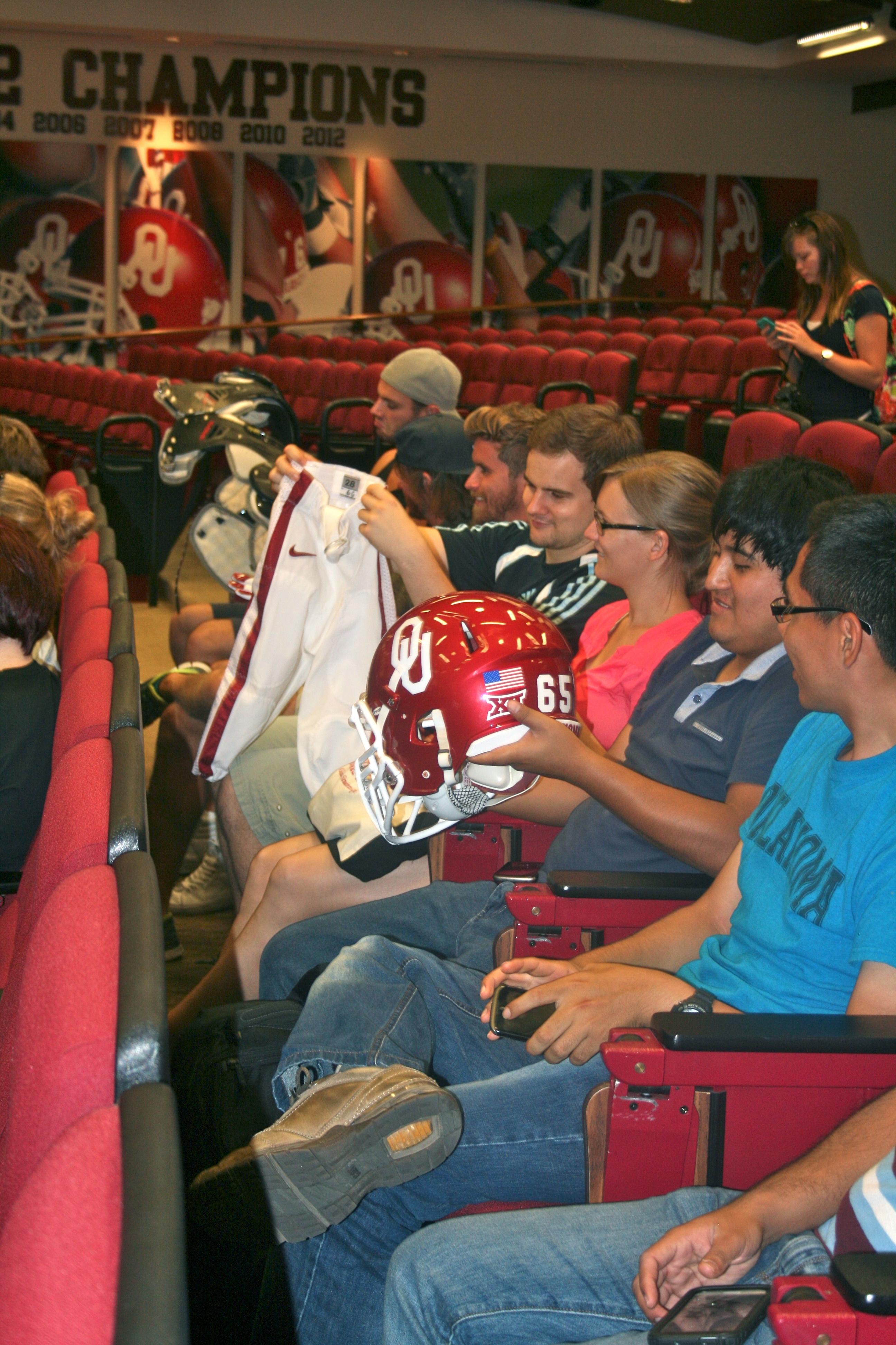Des jeunes assis dans une salles examinent un casque et une tenue de joueur de football américain. (Crédit photo : University of Oklahoma)