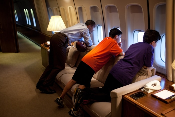 President Obama and two boys looking out aircraft windows (White House)