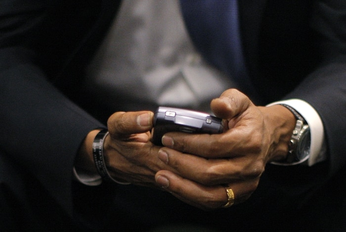 أيد تحمل هاتفا نقالا (© AP Images)