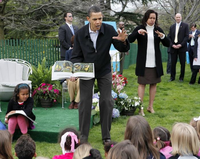 Un livre à la main, Barack Obama raconte une histoire à un groupe d'enfants, en plein air. (© AP Images)