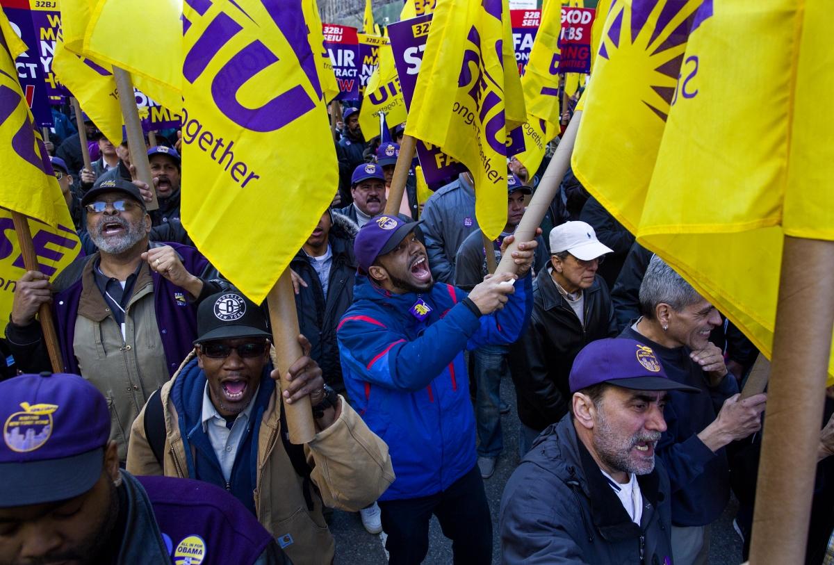Manifestation de syndicalistes, portant des drapeaux de leur syndicat et des pancartes (©AP Images)