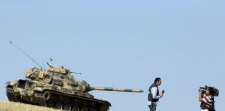 مراسل تلفزيوني ومصور صحفي يصوران تقريرًا بينما تسير خلفهما دبابة (AP Images)