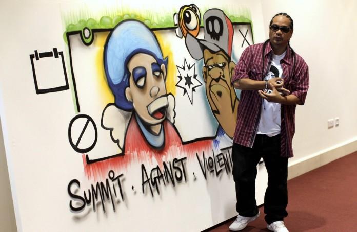 Hombre frente a una caricatura firma en favor de una cumbre contra el extremismo violento (© AP Images)