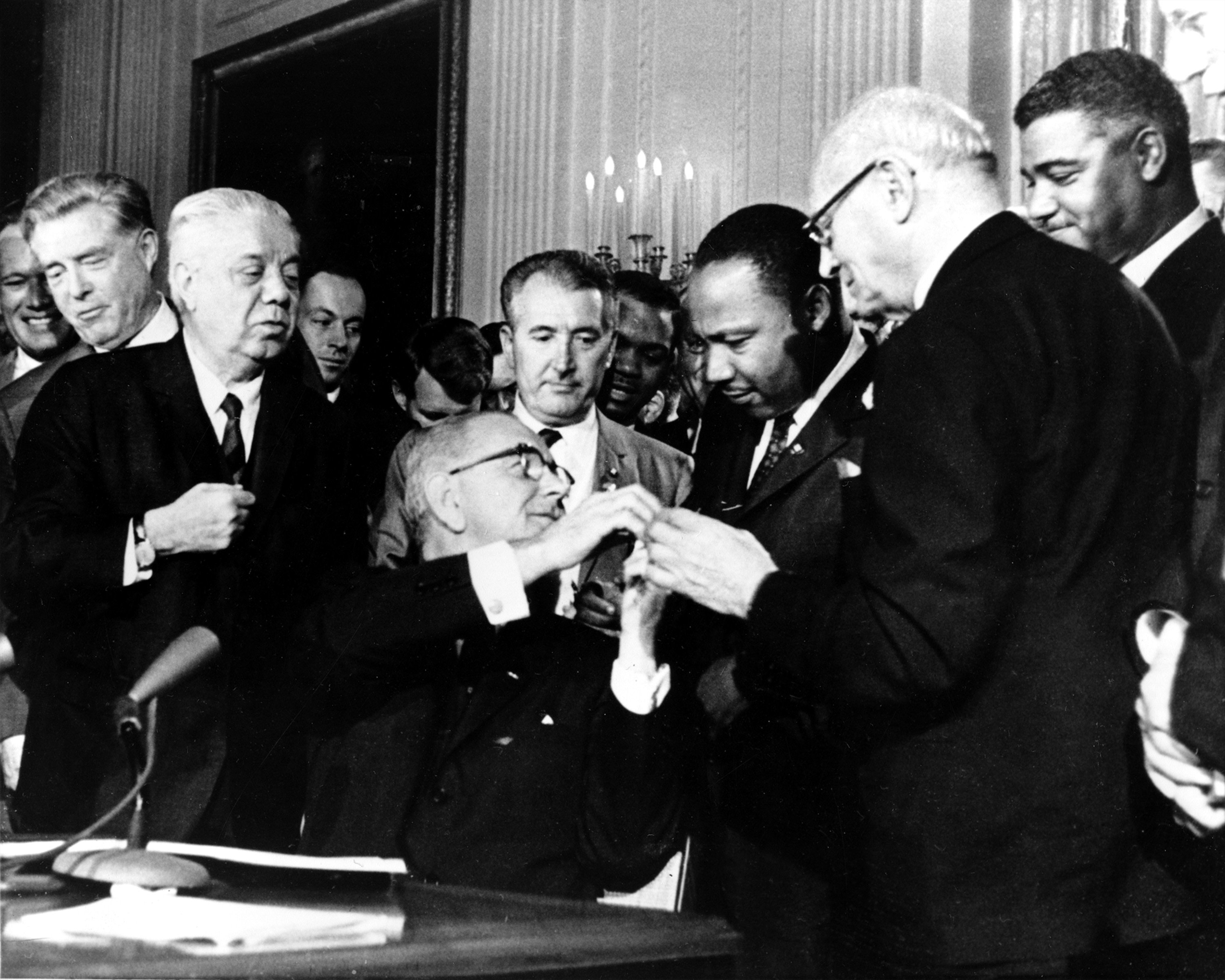 Martin Luther King accepting signing pen from Lyndon Johnson, seated, as others look on (© AP Images)