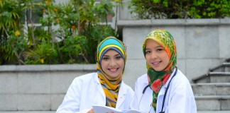شابتان ترتديان الحجاب وسترة مختبر إحداهما تحيط بعنقها سمّاعة طبيب (Shutterstock)