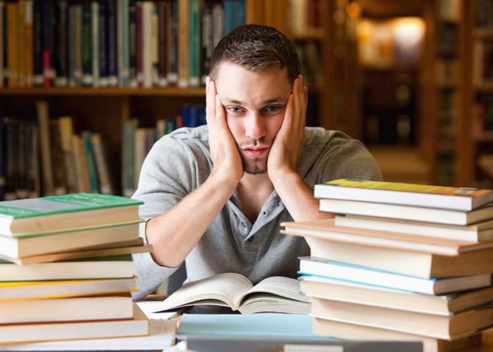 Un étudiant dans une bibliothèque, fatigué, deux piles de livres à côté de lui (Shutterstock)