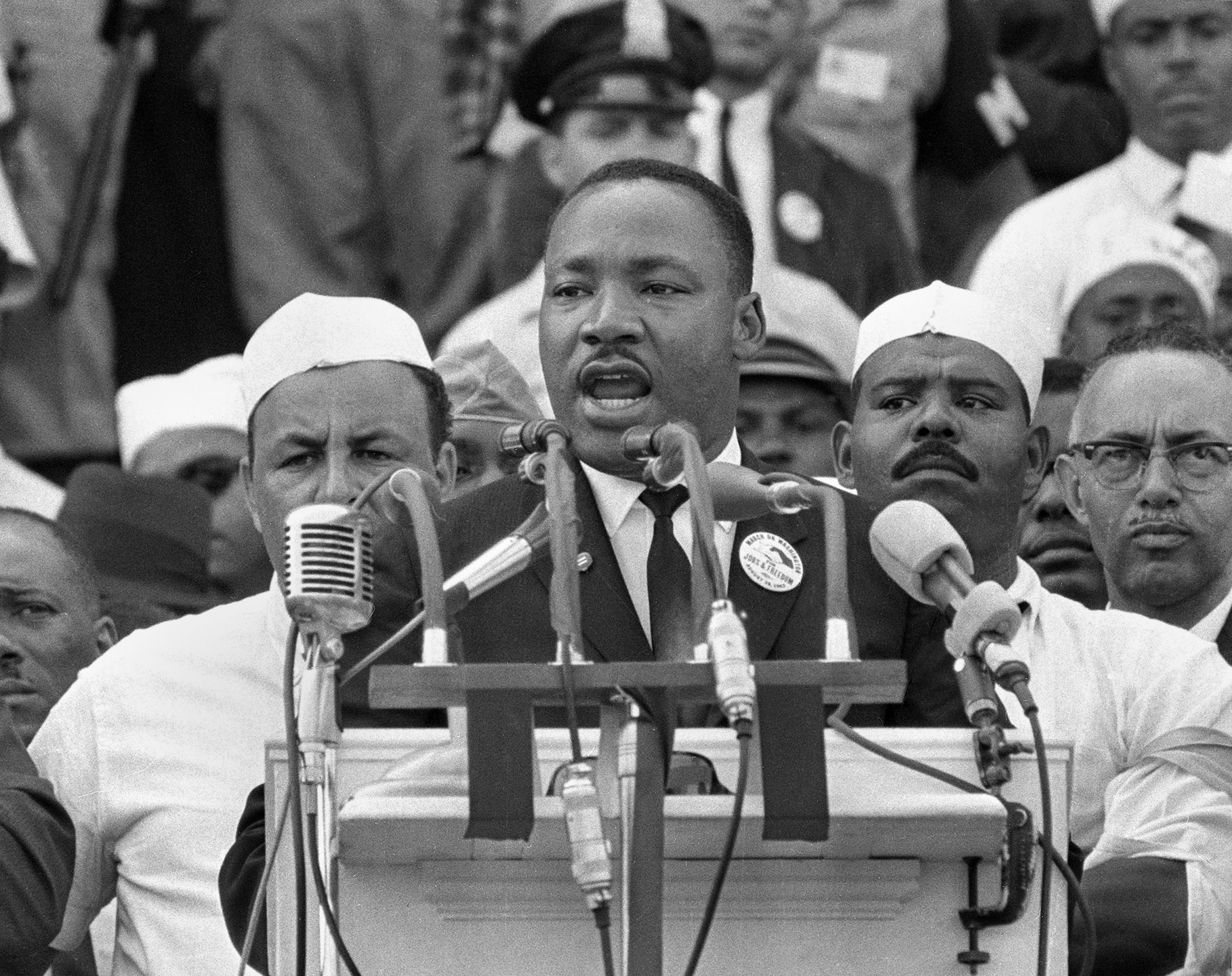 Martin Luther King speaking into row of microphones, crowd behind him (© AP Images)