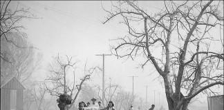 Personas caminando en un camino polvoriento cargando bultos (Archivo Nacional)