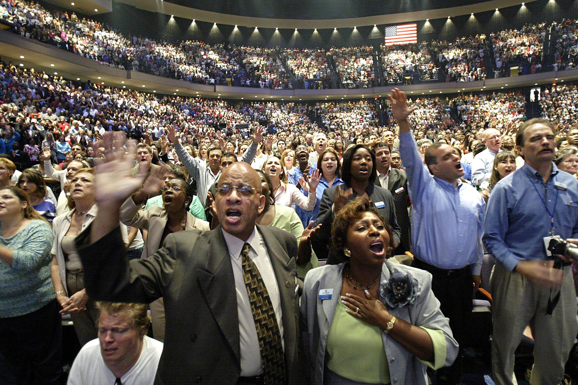 Une grande foule debout, les bras levés © AP Images