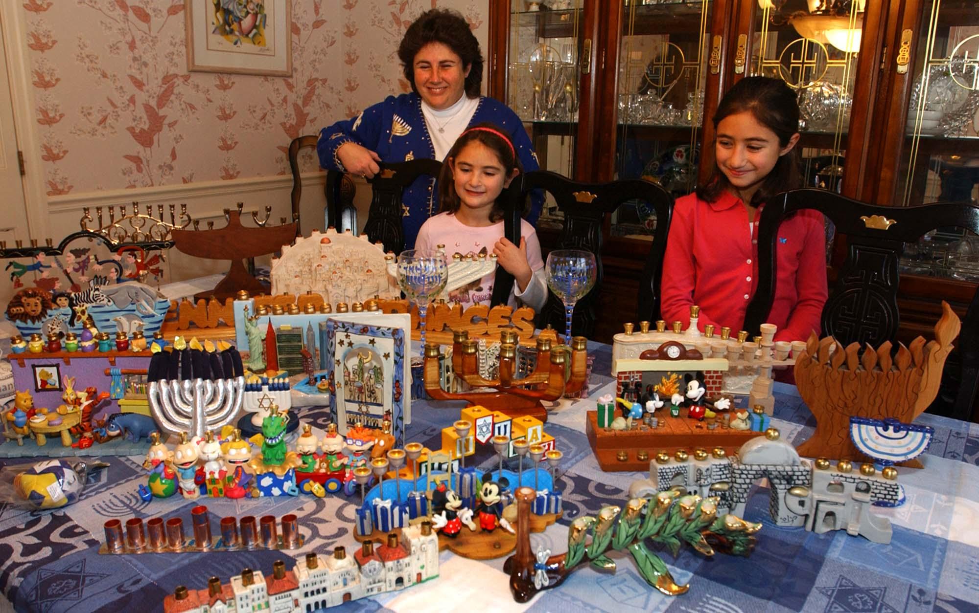 Une femme et deux fillettes debout derrière une table sur laquelle sont posées de nombreuses menorahs. © AP Images