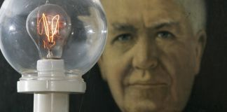 Painting of man behind lit lightbulb (© AP Images)
