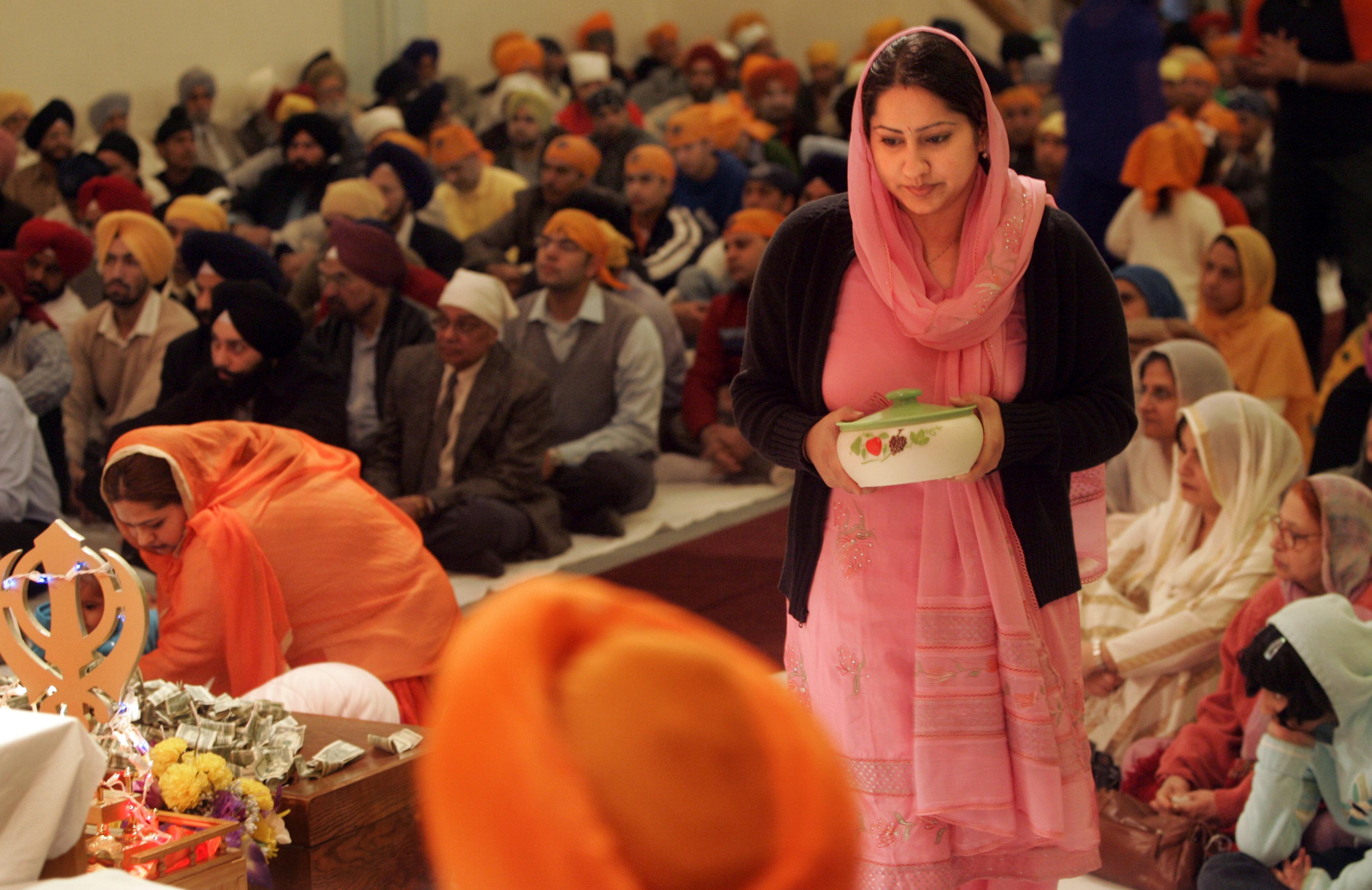 Une femme portant un plat, entourée de fidèles assis par terre © AP Images