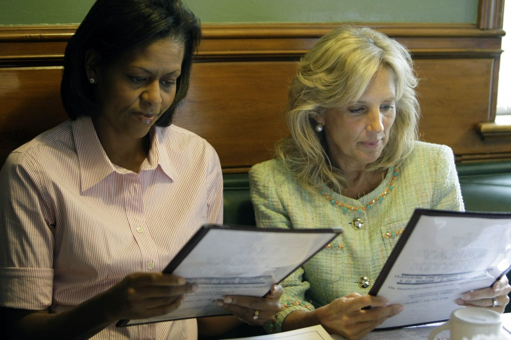Michelle Obama and Jill Biden holding menus (© AP Images)
