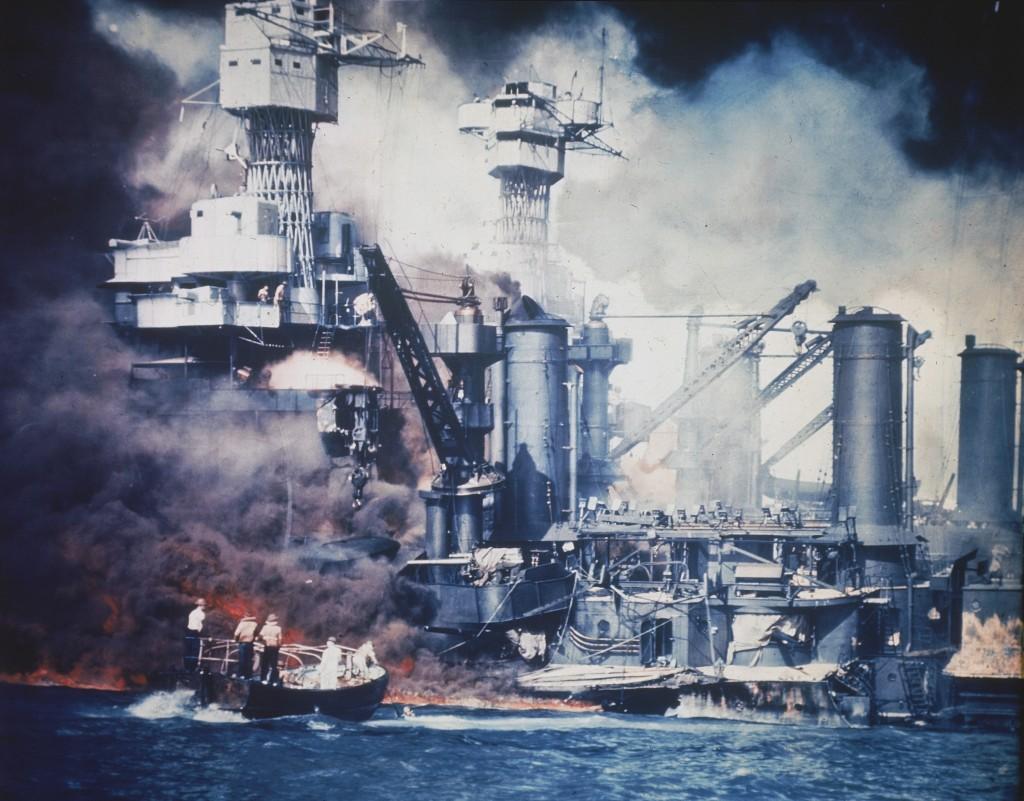 Un voilier et un navire militaire en flammes (© AP Images)