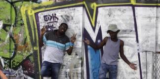 Deux hommes debout devant une porte peinte avec des dessins colorés (© AP Images)