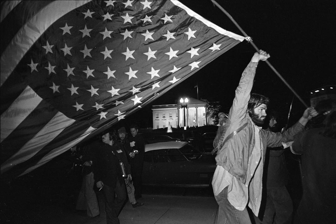 Manifestant brandissant un drapeau américain inversé, avec la Maison Blanche à l'arrière-plan (© AP Images)