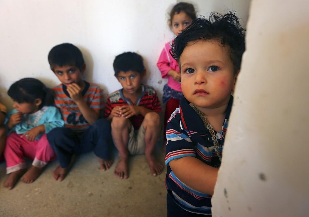 Des enfants irakiens réfugiés, accroupis (© AP Images)