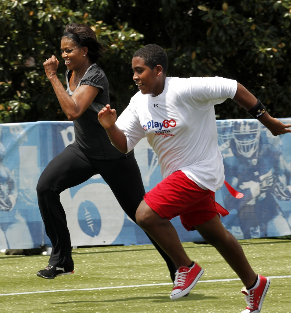 Michelle Obama and a young man running on track (© AP Images)