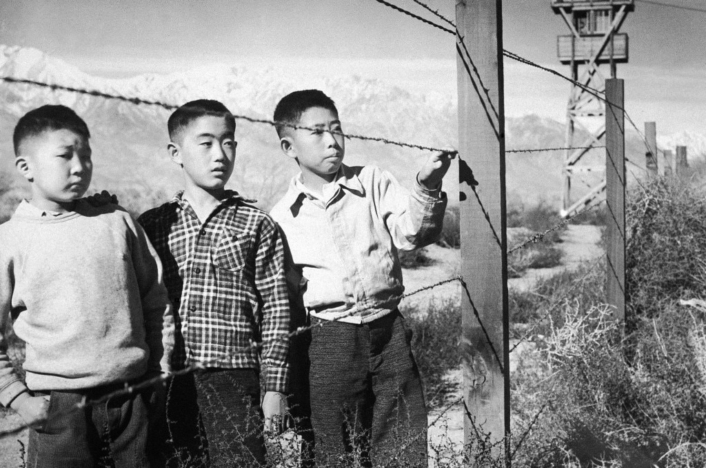 Trois garçons derrière une clôture barbelée dans un camp d'internement d'Américains d'origine japonaise (Archives nationales)