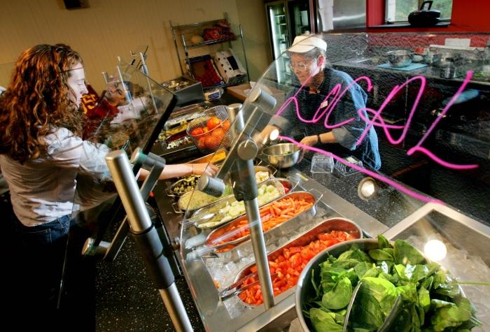 Une jeune femme se sert de la nourriture au comptoir à salades d'une cafétéria, derrière lequel se tient une femme (© AP Images)