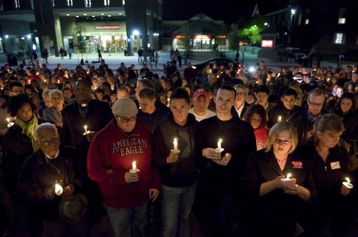 Une foule de personnes rassemblées dans la nuit, des bougies à la main (© AP Images)