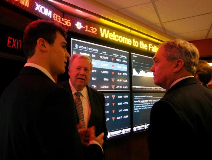 Un jeune homme discute avec deux hommes plus âgés devant des écrans boursiers (© AP Images)