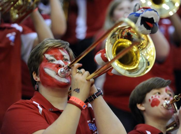 Gros plan sur une jeune femme au visage peint, en train de jouer du trombone (© AP Images)