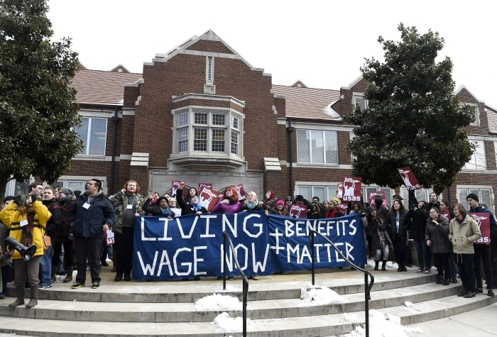 Des personnes en train de manifester avec des pancartes devant un bâtiment (© AP Images)
