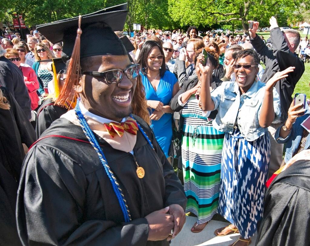 Un jeune homme portant une toque, une robe universitaire et des lunettes de soleil, sourit, avec derrière lui une foule de personnes souriant et applaudissant (© AP Images)
