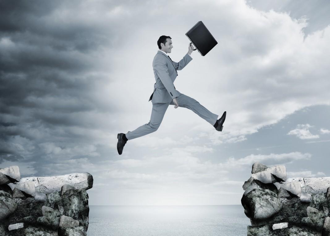 مردی که کیفی در دست دارد و از روی دره ای می پرد (Shutterstock)