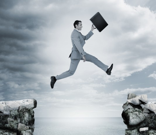 Man jumping across a ravine holding a briefcase.
