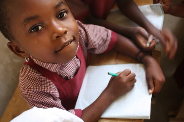 یک دختر در حال نوشتن در دفتر یادداشت خود (کریستا فریدلی/ نان برای جهان)