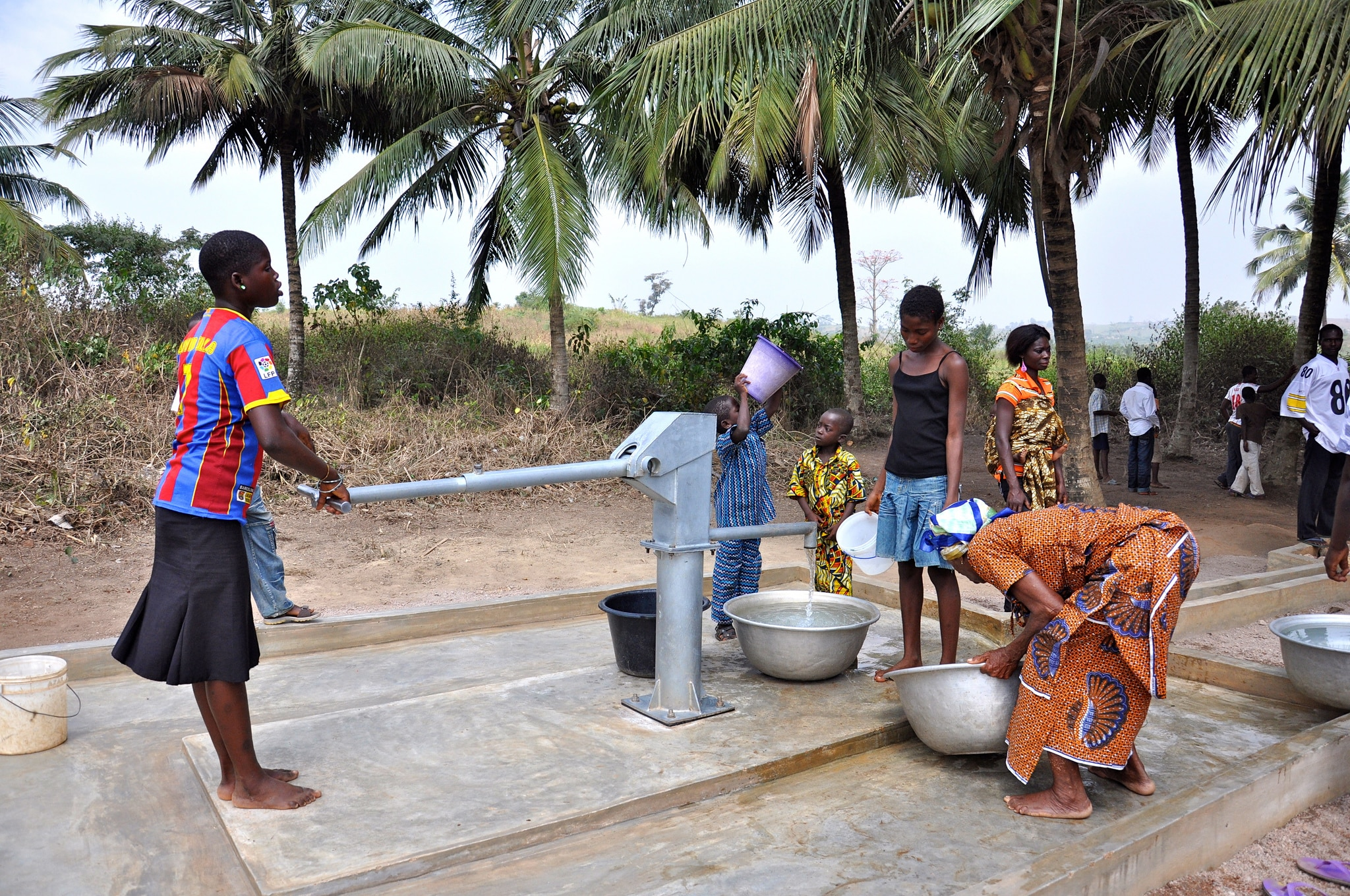 Woman drawing water from pump (USAID)